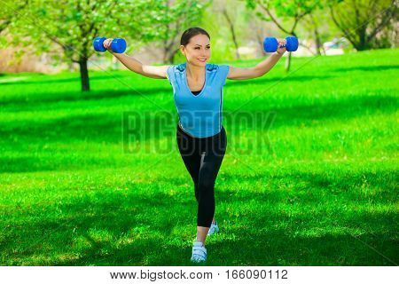 Beautiful athlete involved in sports on the street conducts training with dumbbells in his hands.