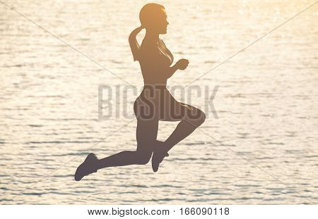 Silhouette of a beautiful slim girl who jumps on a background of a sunset on the beach. The concept of a healthy lifestyle and sports culture.