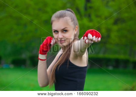 The girl the athlete the boxer in the park also gives the hand compressed in a fist forward with the reeled sports red bandage. Preparation for training. Concept of sport and healthy lifestyle.