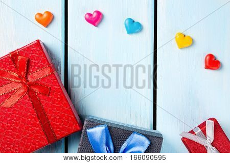 Colorful gift boxes with decorative hearts on nice blue wooden background with free space.