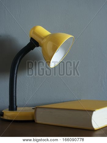 Yellow desk lamp next to the yellow book. Reading room.