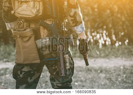 The soldier in the performance of tasks in camouflage and protective gloves holding a gun. War Zone.
