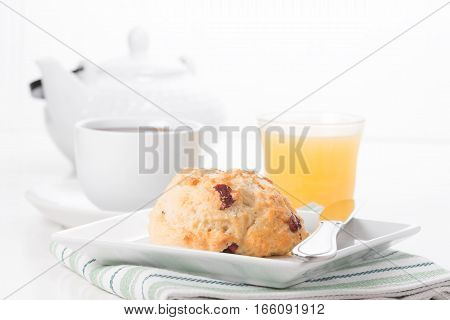 Fresh cranberry lemon scone served with coffee and juice.