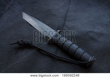 Black knife on a black background for the military.