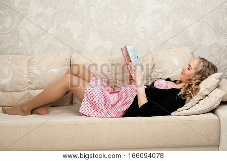 Young beautiful pregnant woman is lying on the back on the couch and reading a book, one hand embracing the belly