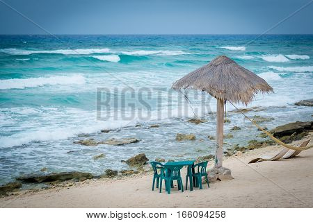 Table set on beach with grass umbrella shade