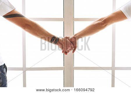 Close up of male hands holding hands with love. Homosexual couple is standing near window