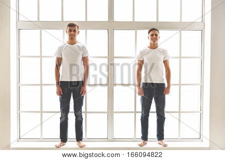 Happy two men are standing on windowsill and smiling