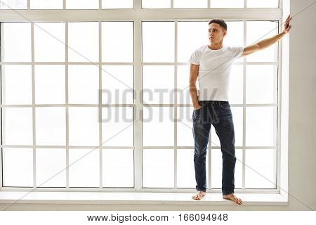 Attractive young guy is waiting for someone. He is standing on windowsill and leaning hand on wall. Guy is looking aside with confidence