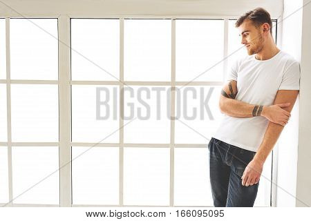 Dreamful shy guy is posing on windowsill with cute smile. He is standing and leaning back on wall