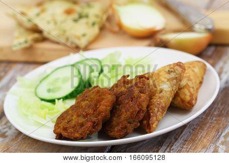 Indian snacks including onion bhajis and samosas, and green side salad