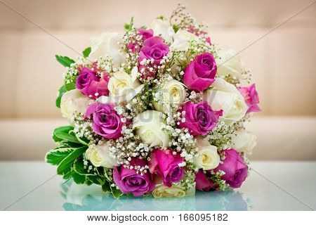 Wedding flower bouquet for the bride in white and purple roses