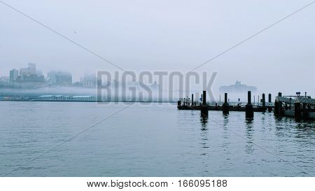 Pier in Lower Manhattan, Brooklyn view. Winter mist.