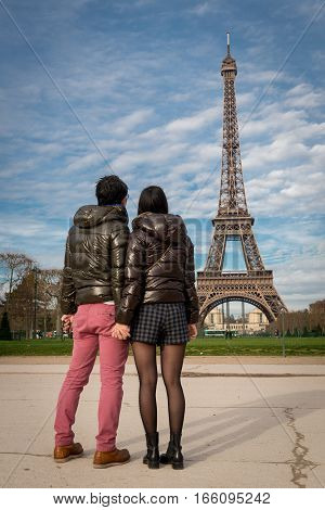 Couple in Paris by Eiffel Tower looking at the tower