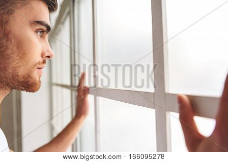 Hopeful anticipation. Pensive young man is standing near window and looking at street with concentration