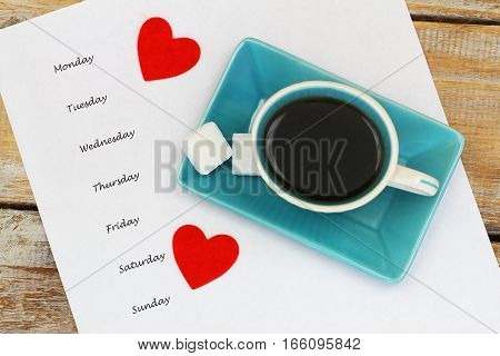 Weekdays listed on white paper, cup of coffee and red hearts