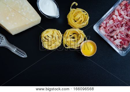 Ingredients for Pasta Carbonara on dark background with place for text. Set of products for pasta Carbonara - pasta bacon cream Parmesan cheese egg. Italian food concept. Copy space. Top view.