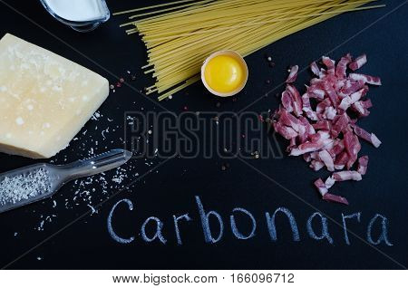 Ingredients for Pasta Carbonara on dark background with word Carbonara. Set of products for pasta Carbonara - spaghetti bacon cream Parmesan cheese egg. Italian food concept. Top view.