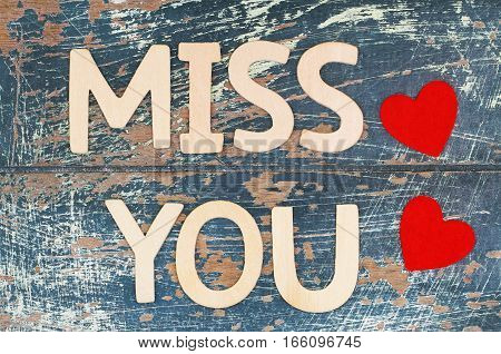 Miss you written with wooden letters on rustic surface and two red hearts