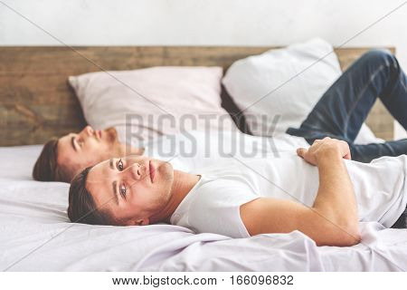 Calm young gays are relaxing on bed together. Man is looking at camera pensively