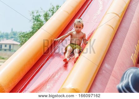Beautiful boy on a red water slide