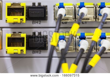 Equipment of radio base station close-up blue and yellow optic patch cords. Internet. Communication. Network