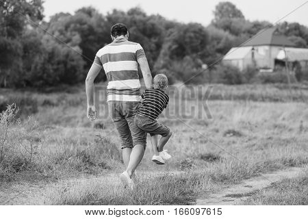 Father playing with his son in the park. Countryside, walk along rural road. Black and white photo.