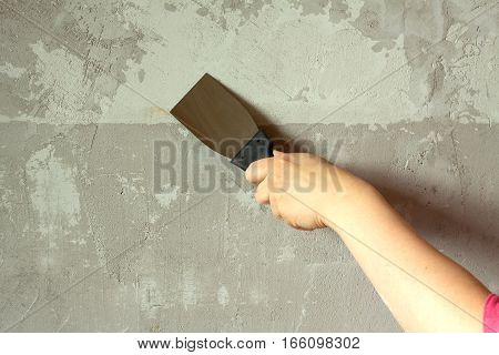 Woman's hand with a spatula concrete wall plasters in room during repair horizontal photo