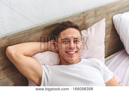 Happy lazy man is lying on bed and smiling. He is looking at camera with joy