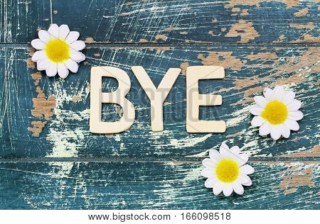 Word bye written with wooden letters on rustic surface and white daisies