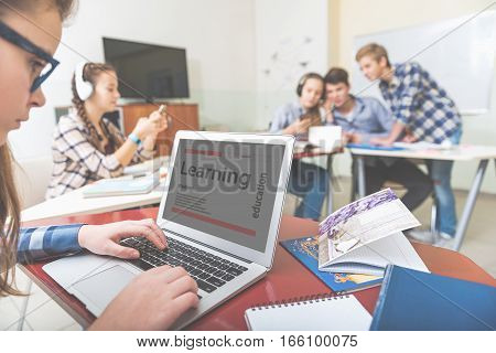 Focus on attentive girl tying at her open laptop. Teenagers are sitting in light room with gadgets