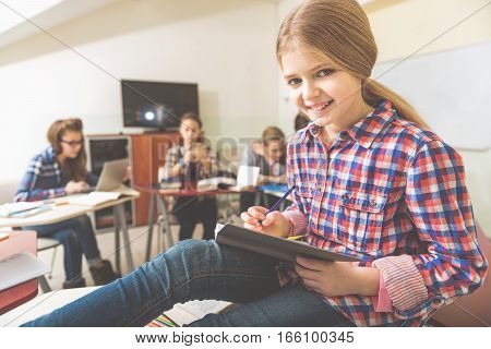 Hilarious female pupil is sitting at desk afore friends. She holding open diary on her knees and looking directly at camera