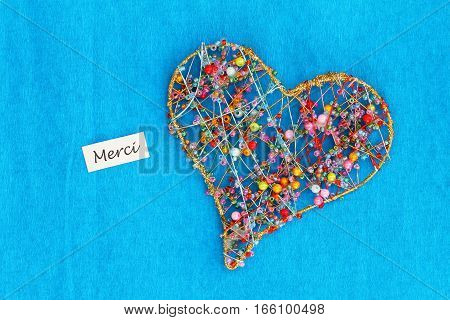 Merci (thank you in French) card with heart made of colorful beads on blue background