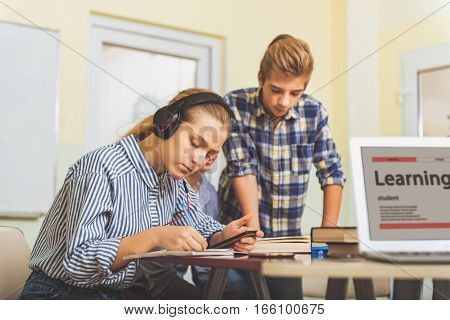Concentrated children are near desks. Focus on absorbedly typing at mobile girl. She is sitting with headphone