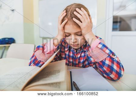Tired female pupil is sitting in classroom near open book on desk. Her eyes are closed. She touching head with hands