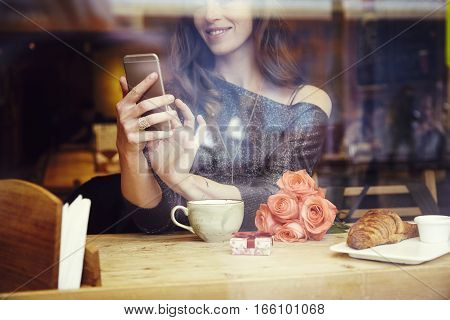 Beautiful caucasian woman with long hair using mobile phone sitting in cafe. Focus on hands. Romantique breakfast for a date or St. Valentine's Day. Present box and rose flowers.