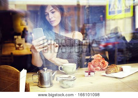 Beautiful caucasian woman with long hair texting message by mobile phone sitting in cafe. Focus on hands. Romantique breakfast for a date or St. Valentine's Day. Present box and rose flowers.
