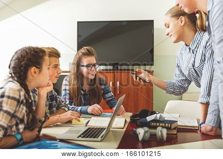Interested teenagers are sitting beside each other near desks. They looking at standing classmates, who using gadget