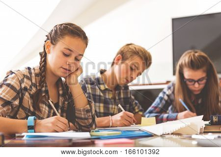 Concentrated pupils are sitting near desk and absorbedly writing information