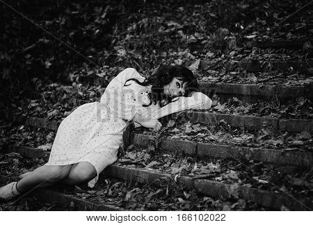 Young Sad Lonely Brunette Girl At Sleepwear Lying On Stairs With Fallen Leaves. Black And White Phot