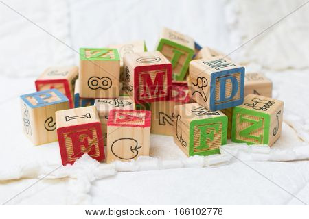 Wooden Alphabet Blocks On Quilt In A Pile