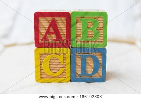 Wooden Alphabet Blocks On Quilt Spelling Abcd Stacked