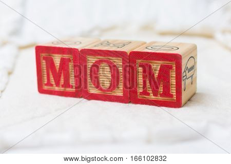 Wooden Alphabet Blocks On Quilt Spelling Mom