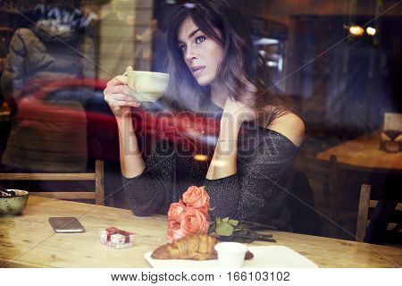 Beautiful caucasian woman with long hair near window in cafe. Drinking coffee Romantique breakfast for a date or St. Valentine's Day. Present box and rose flowers.