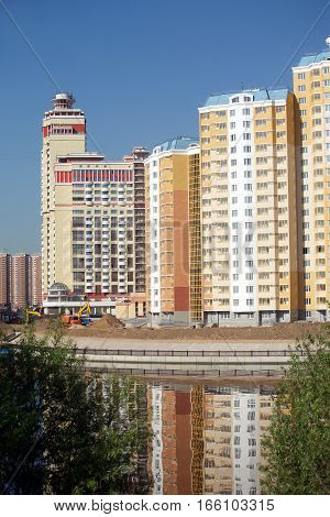 Landscape with new constructed buildings after river over clear blue cloudless sky in summer day
