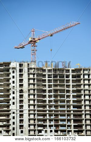 Long hoisting tower crane and top of construction building over cloudless sky