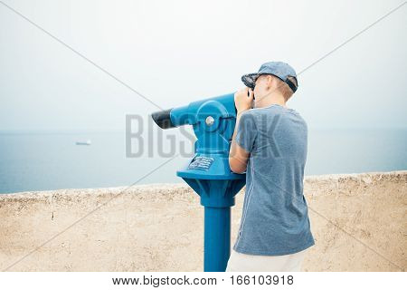Teenager is looking through panorama telescope (works with 1 euro coin) to the city beach. Young man is observing the landscape, watching the sea. Sea view