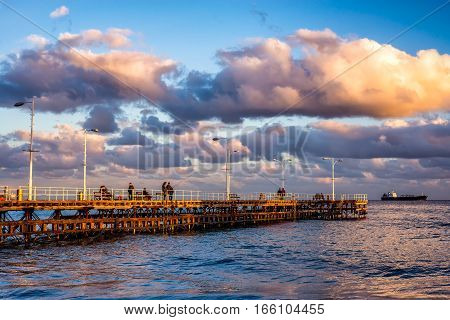 Unidentified people walking the pier on a winter day. Limassol Cyprus.