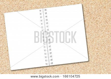 Open notebook paper on cork board background for design with copy space for text or image.