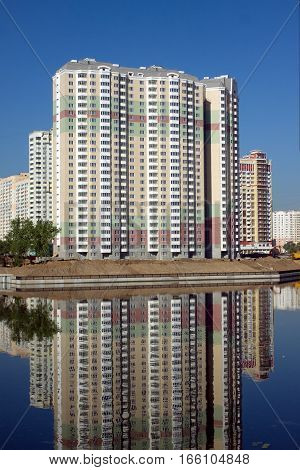 Landscape with many new constructed block of flats after river over clear blue cloudless sky in summer day